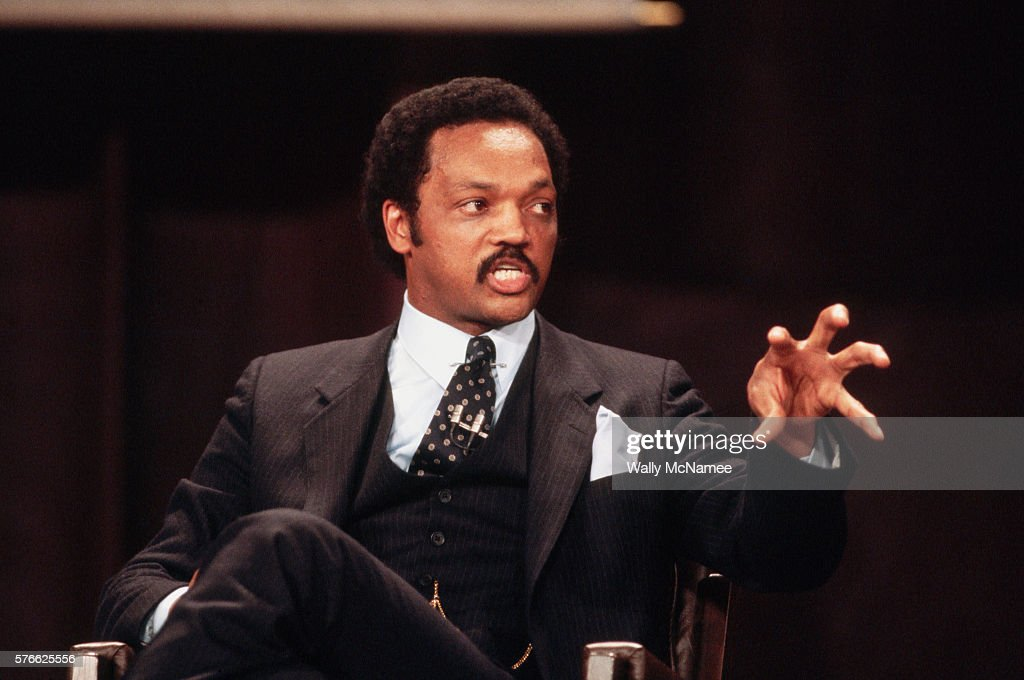Presidential candidate Jesse Jackson gestures as he speaks at a debate with fellow candidates Gary Hart and Walter Mondale