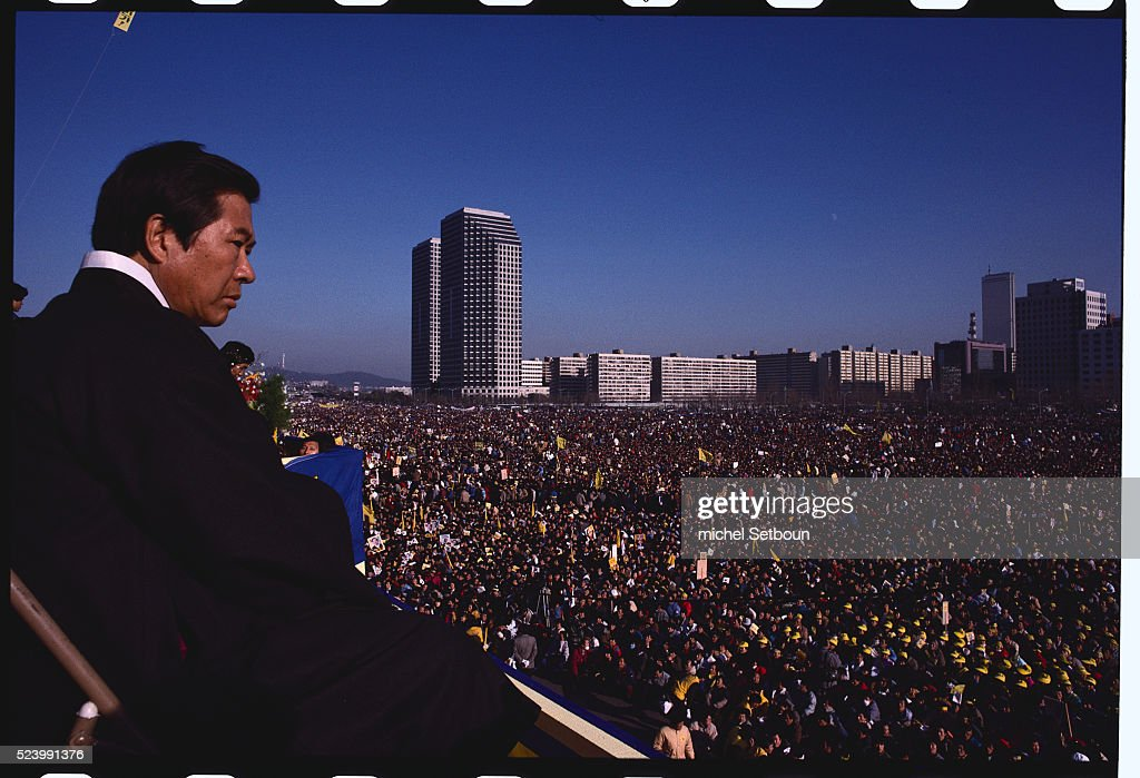 Presidential candidate Kim Dae-jung looks down at a crowd of supporters in the Yoido district of Seoul. He is running in the 1987 South Korean presidential election.