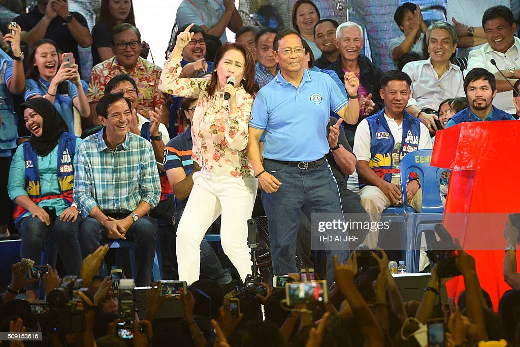 Presidential candidate of the opposition party and current vice-president Jejomar Binay (R) dances on stage with Philippine comedian queen Ai-ai Delas Alas during a proclamation rally in Manila on February 9, 2016. A cliffhanger race to lead the Philippines began February 9 with emotion-charged rallies by a dead movie star's adopted daughter, a politician who brags about killing criminals and other top contenders. AFP PHOTO / TED ALJIBE / AFP / TED ALJIBE