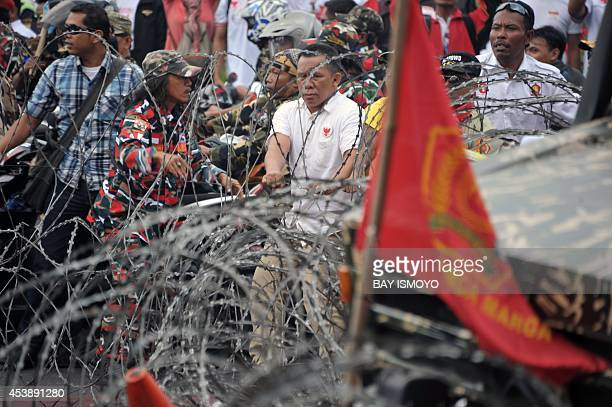 Presidential candidate Prabowo's supporters try to pass police blockade near the constitutional court in Jakarta on August 21 where the court will...