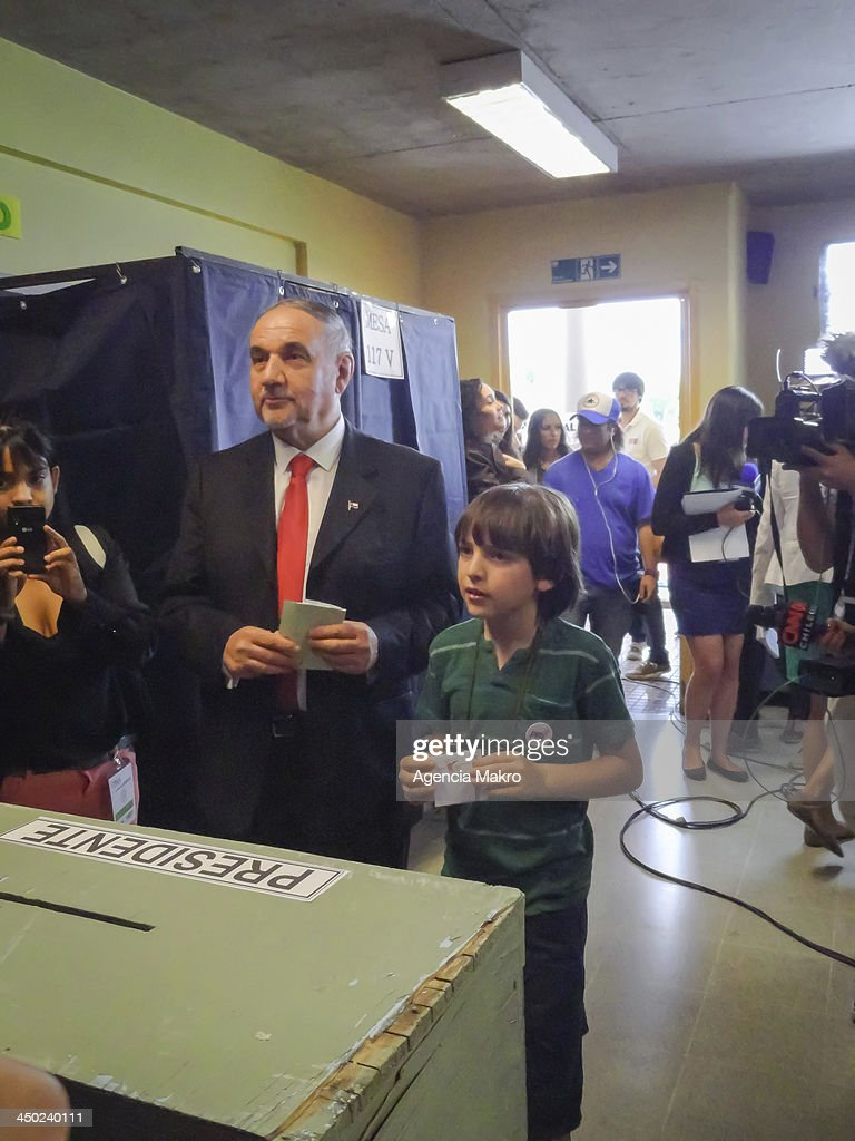 Presidential candidate Ricardo Israel casts his vote at the polls next to his son at John Paul II school on November 17, 2013 in Santiago, Chile.