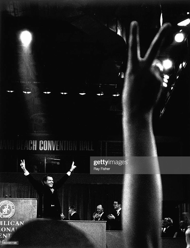 Presidential candidate Richard Nixon at podium (rear) at Republican Convention with both hands up in v-symbols with spectator giving the peace sign in foreground.