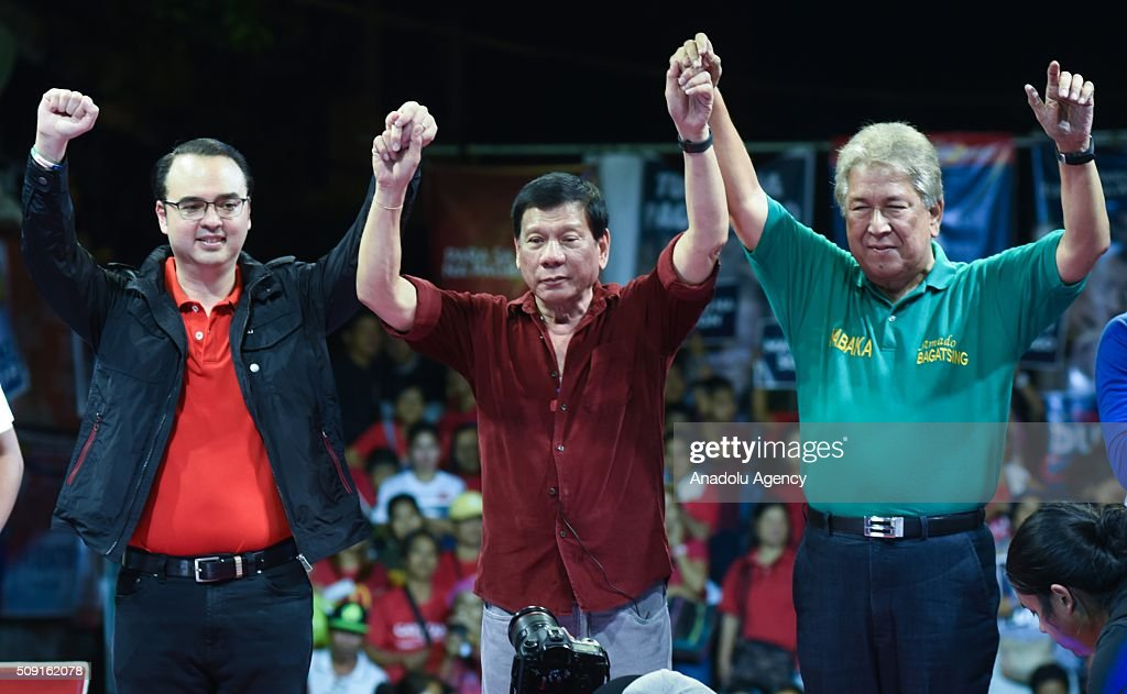Presidential candidate Rodrigo Duterte (center) and vice presidential candidate Allan Peter Cayetano (L) poses for photos during their proclamation rally in Manila on February 9, 2016. Duterte is well known for being the crime fighting mayor of Davao City, southern Philippines.