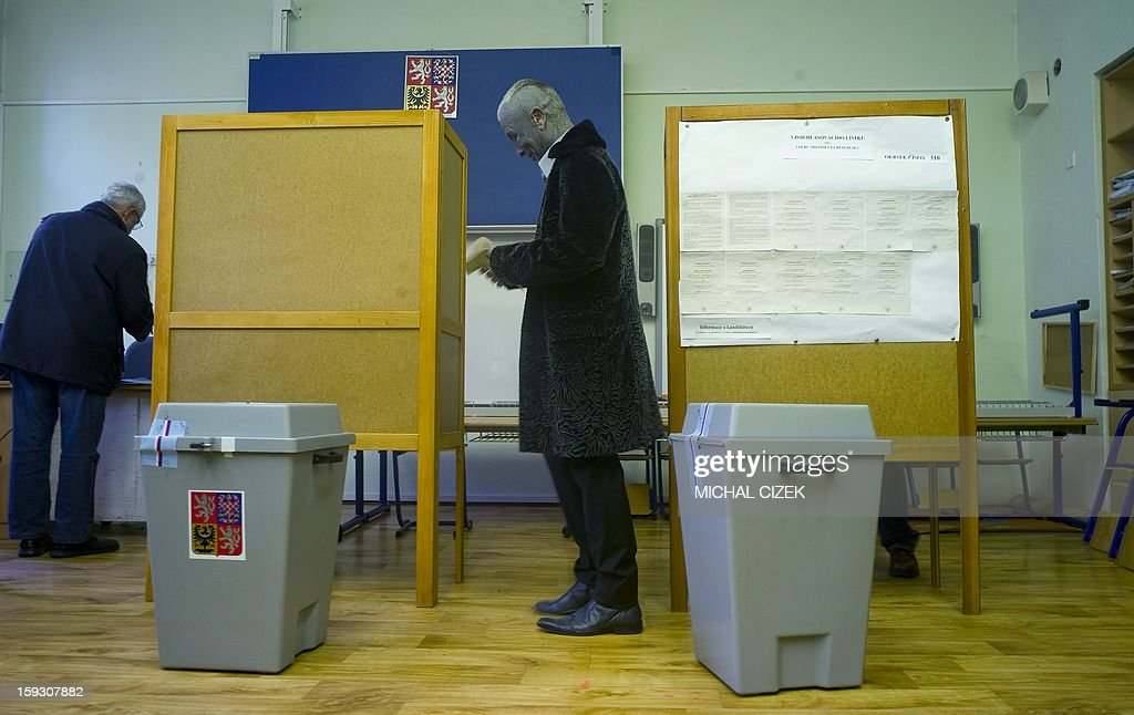 Presidential candidate Vladimir Franz (C) holds his ballot at a polling station in Prague on January 11, 2013. Czech polling stations were opened on January 11 afternoon in local mid-time for the first round of the first Czech direct presidential election in history. AFP PHOTO / MICHAL CIZEK
