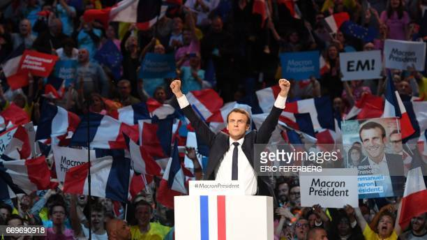TOPSHOT Presidential election candidate for the En Marche movement Emmanuel Macron raises his fists on stage during a campaign meeting on April 17...