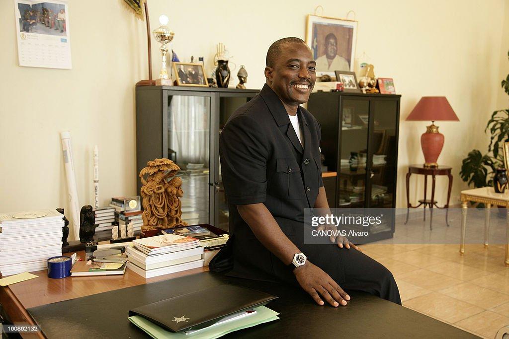 Presidential Elections In The Democratic Republic Of Congo. Attitude souriante du président Joseph KABILA assis sur un coin d'une table dans son bureau présidentiel au palais de la Nation à KINSHASA à deux jours du deuxième tour des élections présidentielles qui le donne favori face à Jean-Pierre Bemba (on voit en arrière plan, accrochée au mur, une photo de son père Laurent-Désiré Kabila assassiné le 16 janvier 2001).