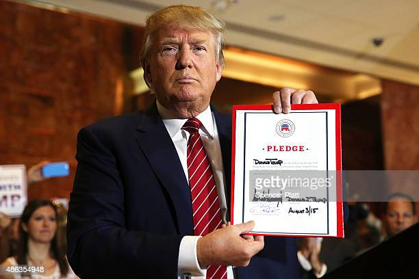 GOP presidential frontrunner Donald Trump holds up a pledge at a news conference in Manhattan after he signed the pledge Thursday to support the...