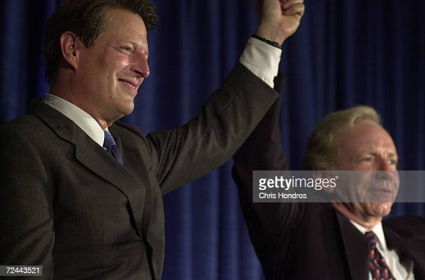 Presidential hopeful Al Gore left clenches hands with his vice presidential running mate Joseph Lieberman at a rally August 9 in Lieberman's hometown...