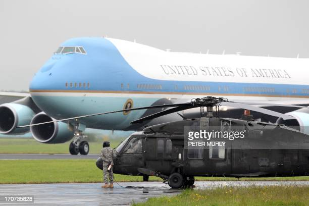 US presidential plane Air Force One arrives as a US blackhawk military helicopter stands guard at Belfast International airport in Belfast Northern...