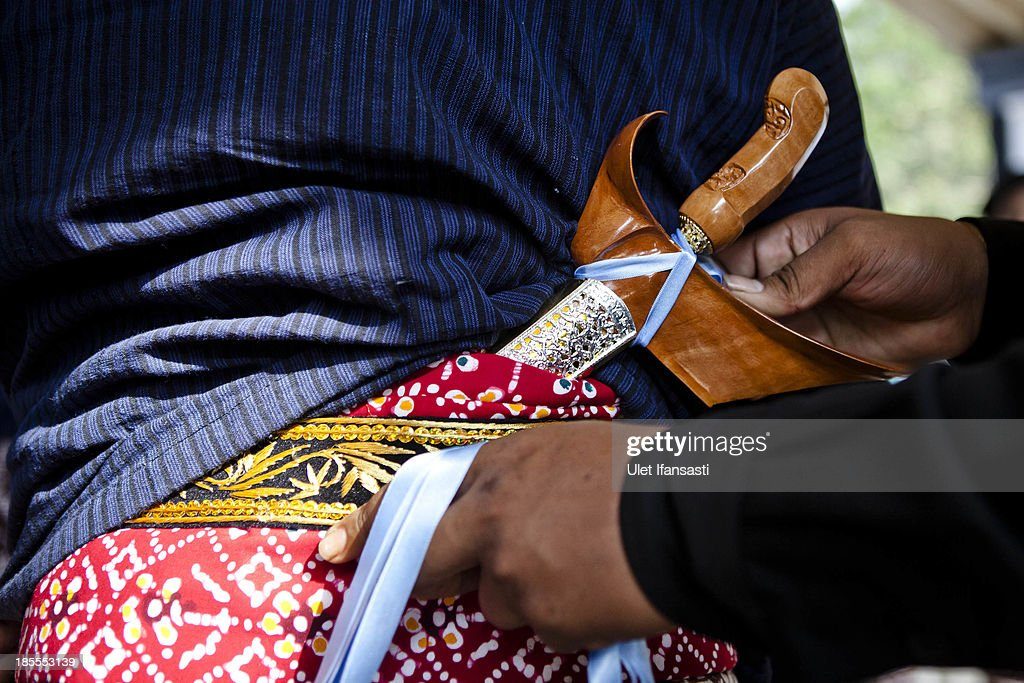 A presidential security officer ties a Keris during the Royal Wedding Held For Sultan Hamengkubuwono X's Daughter Gusti Ratu Kanjeng Hayu And KPH Notonegoro on October 22, 2013 in Yogyakarta, Indonesia. Wedding celebrations will take place October 21-23 October. The wedding parade will include 12 royal horse drawn carriages and will be streamed live on the internet so that it can be watched by people all over the world.