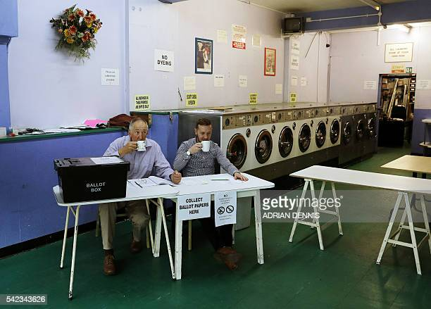 TOPSHOT A presiding officer and poll clerk drink a cup of tea while waiting for early morning voters at a polling station set up in a launderette in...