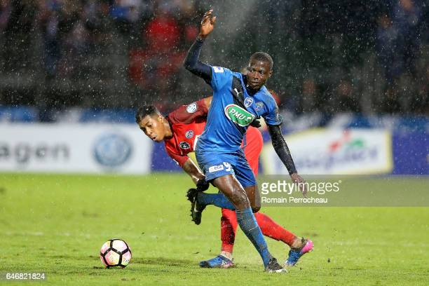 Presnel Kimpembe of Paris Saint Germain and Ande Dona Ndoh of Niort in action during a French Cup match between Niort and Paris Saint Germain at...