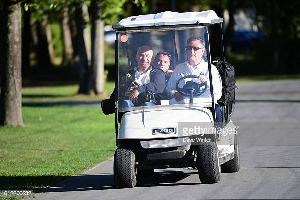 Press attache Philippe Tournon gives photographers a lift to the training session of the French team at the Centre National du Football on October 3...