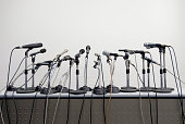 A large group of microphones set up on a table for a press conference or public speaking event.
