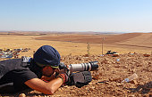 A press member is seen as the clashes between ISIL militants and the Kurdish armed groups continue on October 1 2014 in Zorafa region between Tell...