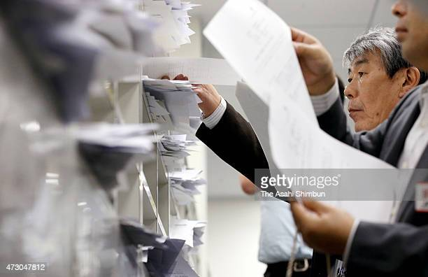 Press officers of companies post the financial result documents at Kabuto Club press club in the Tokyo Stock Exchange on May 12 2015 in Tokyo Japan