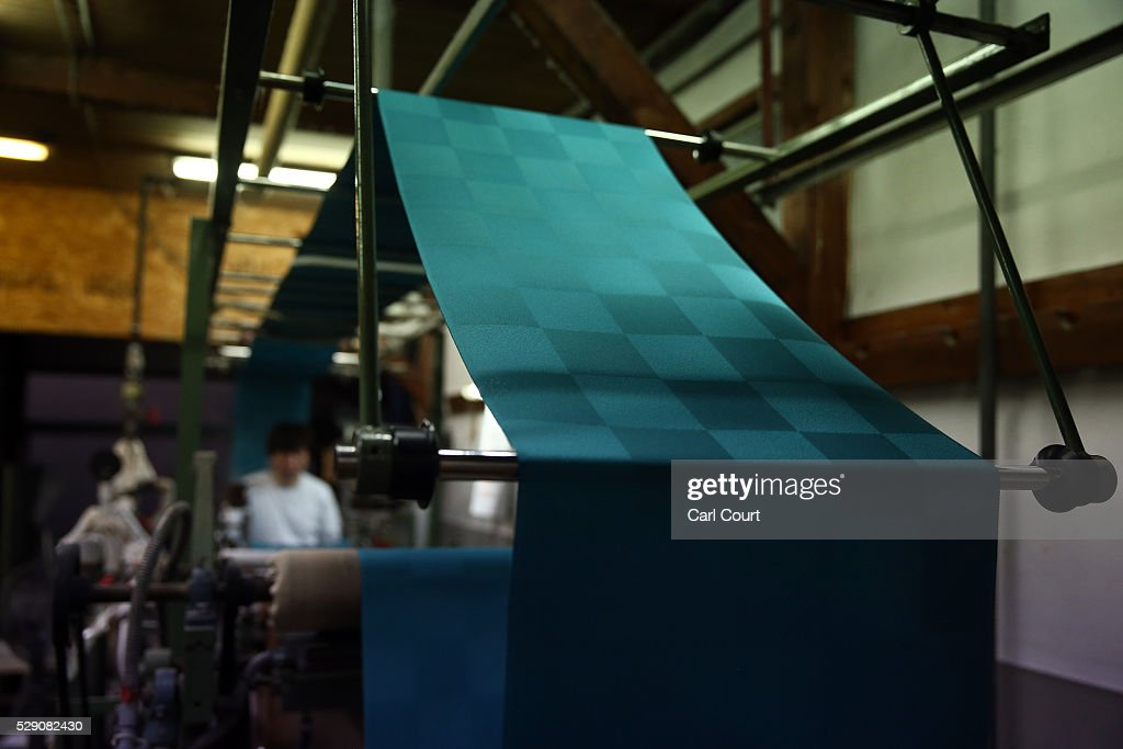 A press operator oversees kimono fabric being pressed flat after the painting and dyeing process where it is often creased during a stage of its...