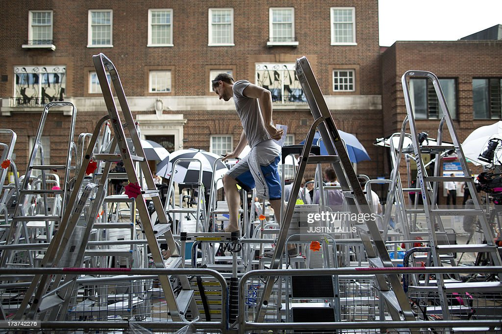 A press photographer climbs over ladders to look at his position outside the Lindo Wing of Saint Mary's Hospital in London, on July 17, 2013, where Prince William and his wife Catherine's baby will be born. Queen Elizabeth II, it seems, is just as impatient as her subjects for the royal baby to arrive this week -- because she is going on holiday. AFP PHOTO / JUSTIN TALLIS