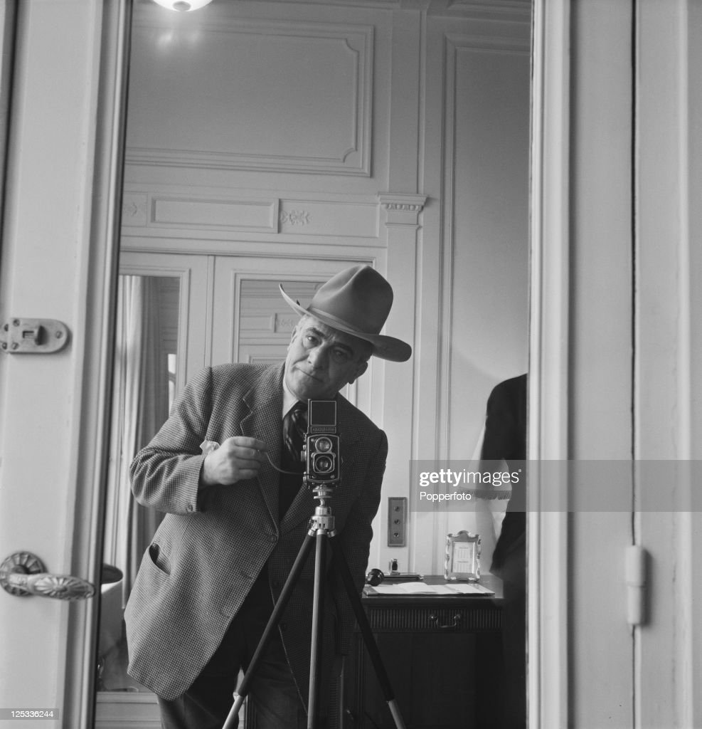 Press photographer James Jarche (1891 - 1965), of 'Illustrated' magazine, uses a Rolleiflex camera on a tripod to take a self-portrait in a mirror at the Savoy Hotel, London, 1951. Jarche is at the Savoy to photograph American actor John Wayne.