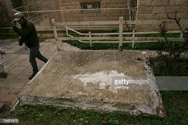 A press photographer pass by a concrete slab marks the covered entrance to a 1st century burial tomb that was excavated by Israeli archaeologists in...