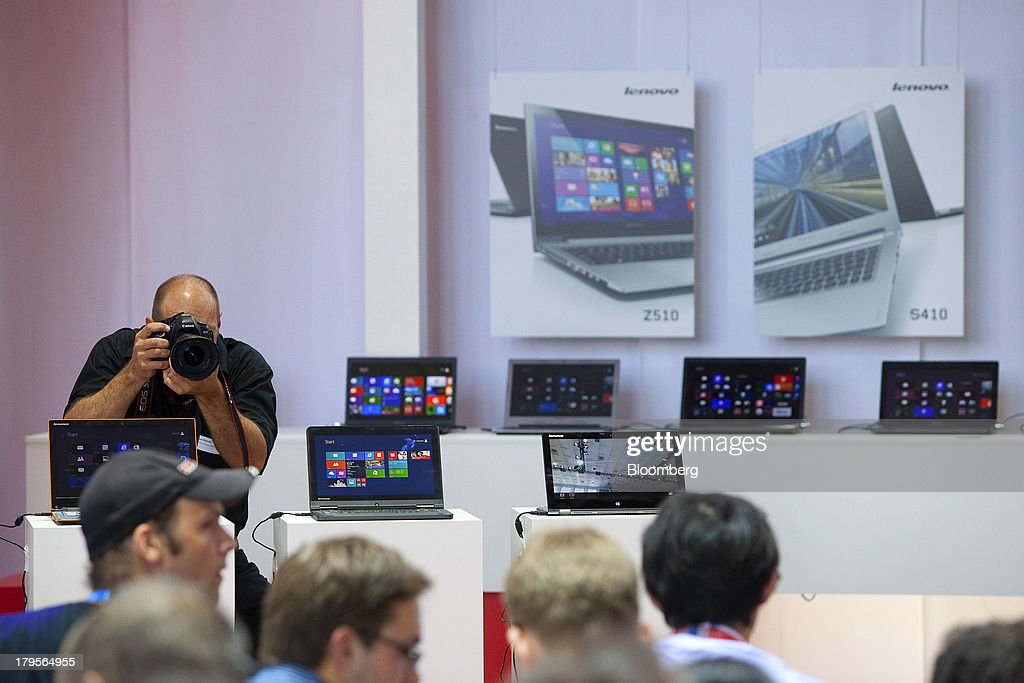 A press photographer takes photos as he stands behind laptops manufactured by the Lenovo Group Ltd on the eve of the opening of the IFA consumer electronics show in Berlin, Germany, on Thursday, Sept. 5, 2013. Samsung showed the Galaxy Gear yesterday at IFA, Europe's largest consumer-electronics show, as it races Apple and Sony Corp. to carve a share of the market for wearable technology amid slowing growth in smartphones. Photographer: Krisztian Bocsi/Bloomberg via Getty Images