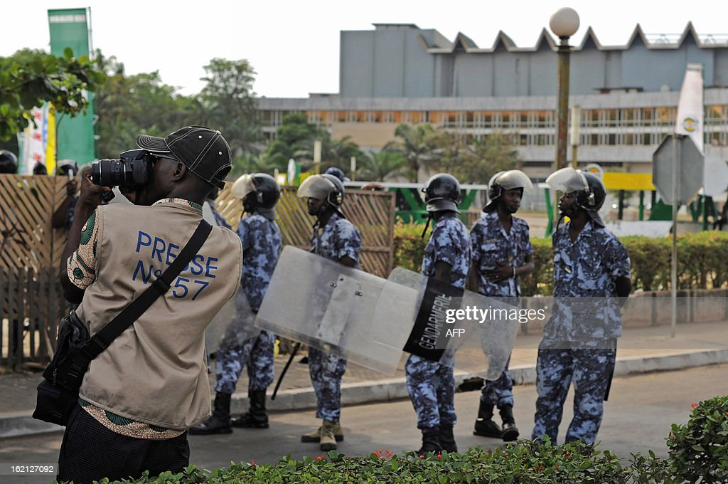 A press photographer takes pictures of protestors as security forces stand behind to prevent a crowd of several hundred journalists and members of the public from protesting in front of the Palais des Congres in Lome on February 19, 2013. Journalists in Togo are protesting against a law giving the High Authority of Audiovisual and Communication (HAAC) more power to control media in Togo.