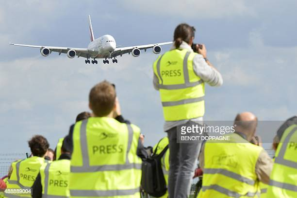 Press photographers look at the arrival of the Emirates A380 Airbus the biggest passenger airplane in the world on September 18 2015 at the Brussels...