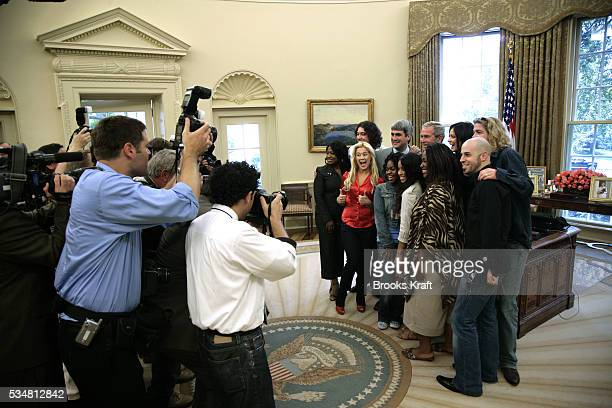 Press photographers scramble for position as US President George W Bush gathers with the top nine American Idol 2006 finalists in the Oval Office of...
