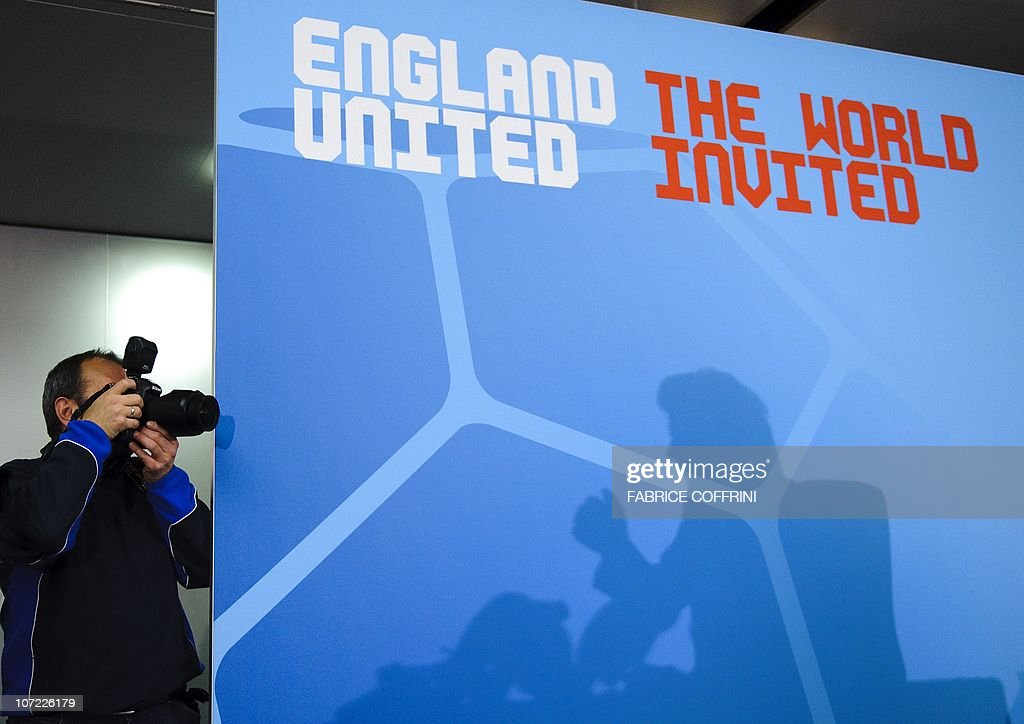 A press photographers take pictures of English football icon David Beckham whose shadow is cast on the backdrop of a press conference on December 1...