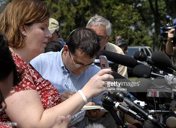 Press Secretary for the Governor of Kentucky Jodi Whitaker holds up a cell phone to broadcast Governor Ernie Fletcher's call from Germany to address...