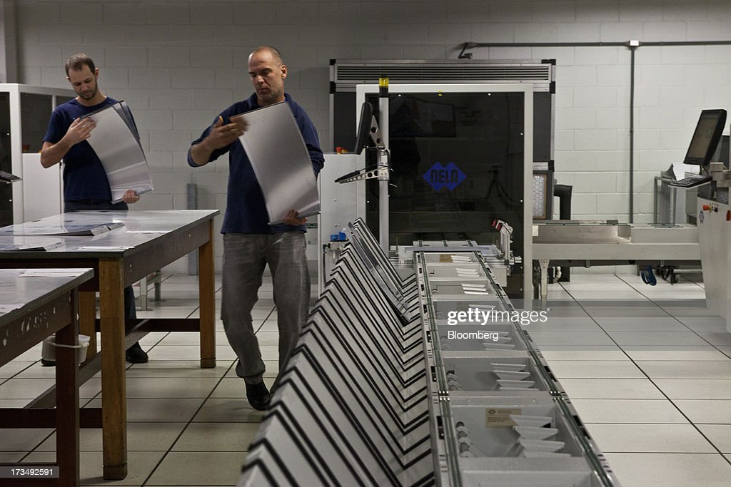 Press technicians inspect the aluminum plates that will be used to print the paper at the press park of O Globo newspaper in Rio de Janeiro, Brazil, on Thursday, July 11, 2013. Brazil economists raised their 2014 benchmark interest rate forecast to the highest all year, as policy makers work to slow inflation that has curbed consumption and confidence in the world's second-biggest emerging market. Photographer: Dado Galdieri/Bloomberg via Getty Images