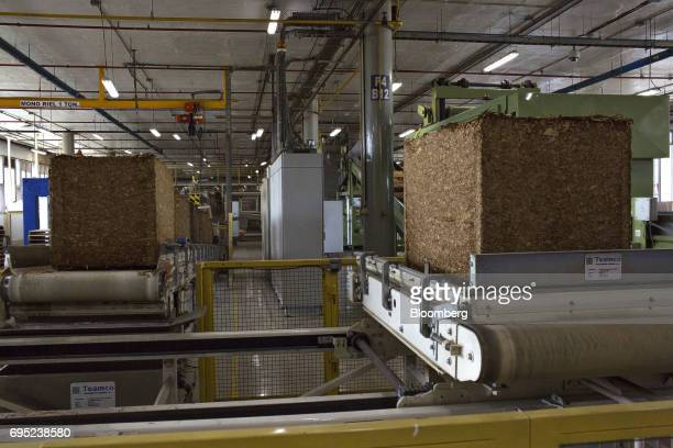 Pressed tobacco cubes move along a conveyor belt at the Philip Morris International Coltabaco SAS production facility in Medellin Colombia on Friday...