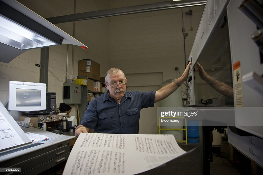 Pressman Kendal Harvey pulls out a sheet in order to inspect the quality of the printing during a print run of sheet music at the Hal Leonard Corp. printing facility in Winona, Minnesota, U.S., on Friday, March 22, 2013. Hal Leonard is the world's largest print music publisher, distributing more than 200,000 titles to over 65 countries. Photographer: Ariana Lindquist/Bloomberg via Getty Images