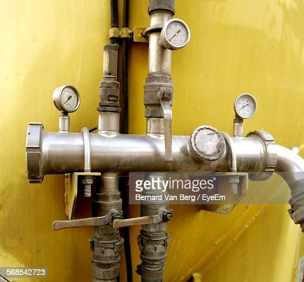 Pressure Gauge On Pipes Against Wall In Factory