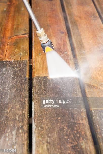 Hochdruckreiniger gereinigt einen verwitterten Deck