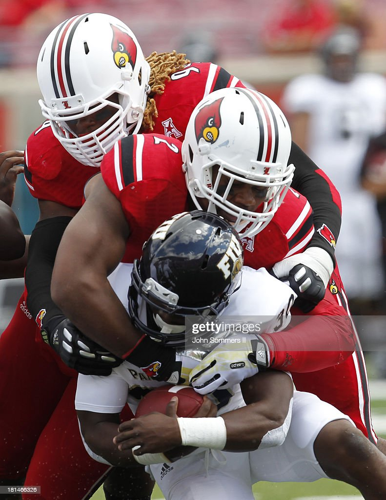 Preston Brown #2 and Lorenzo Mauldin #94 of the Louisville Cardinals tackles Silas Spearman #30 of the Florida International Panthers at Papa John's Cardinal Stadium on September 21, 2013 in Louisville, Kentucky.