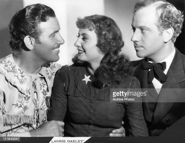 Preston Foster looks at Barbara Stanwyck while Melvyn Douglas watches both in a scene from the film 'Annie Oakley' 1935