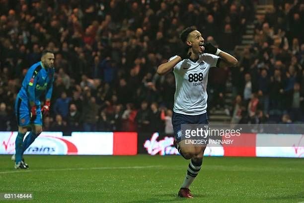 Preston's English striker Callum Robinson celebrates after scoring the opening goal as Arsenal's Colombian goalkeeper David Ospina reacts during the...