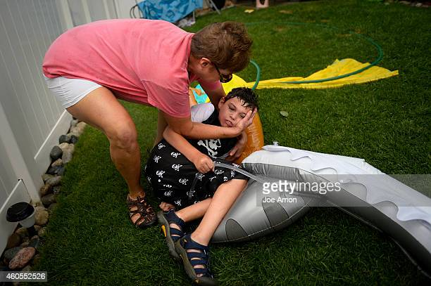 Preston's grandmother 'Oma' Milly Raynor supports his head as she tries to untangle him from a hose he tripped over and a seizure kicks in The pain...