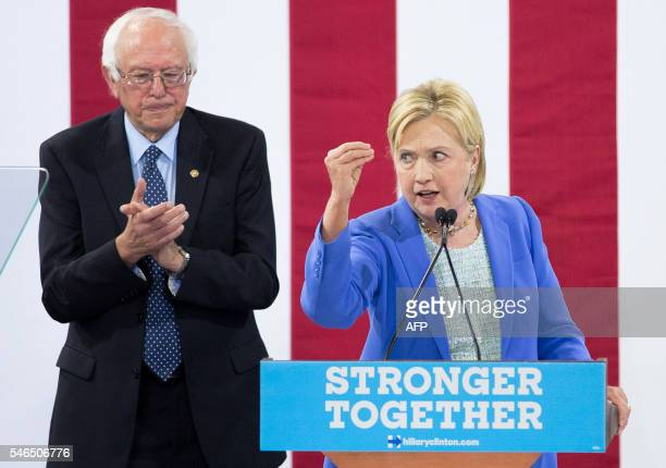 Presumptive Democratic presidential candidate Hillary Clinton makes a point as Bernie Sanders applauds July 12 2016 at a rally in Portsmouth New...