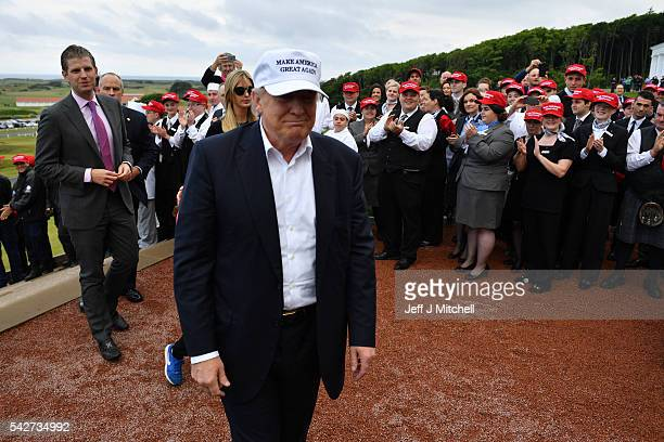 Presumptive Republican nominee for US president Donald Trump arrives to his Trump Turnberry Resort with his son Eric Trump as supports clap on June...