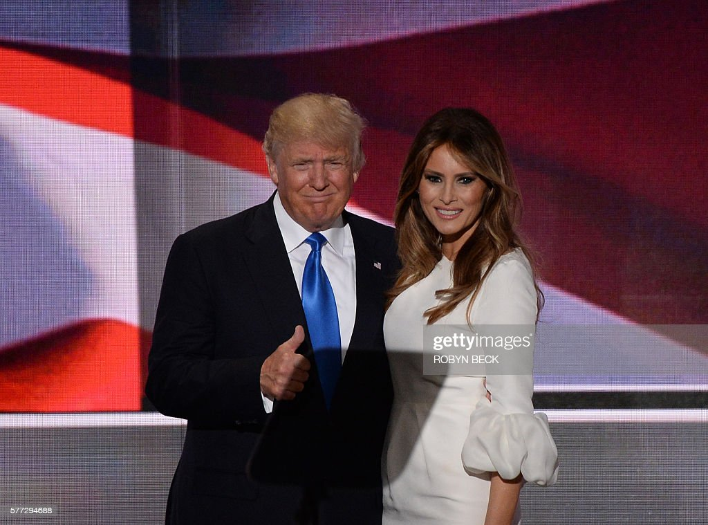 TOPSHOT - Presumptive Republican presidential candidate Donald Trump stands on stage with his wife Melania Trump following her address to delegates on the first day of the Republican National Convention on July 18, 2016 at Quicken Loans Arena in Cleveland, Ohio. The Republican Party opened its national convention, kicking off a four-day political jamboree that will anoint billionaire Donald Trump as its presidential nominee. / AFP / Robyn BECK