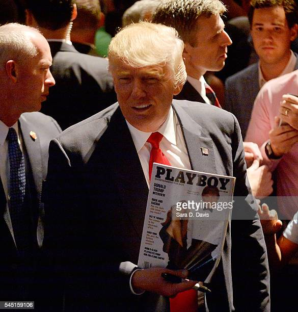 Presumptive Republican presidential nominee Donald Trump shows a police officer his photo on the cover of a Playboy magazine during a campaign event...