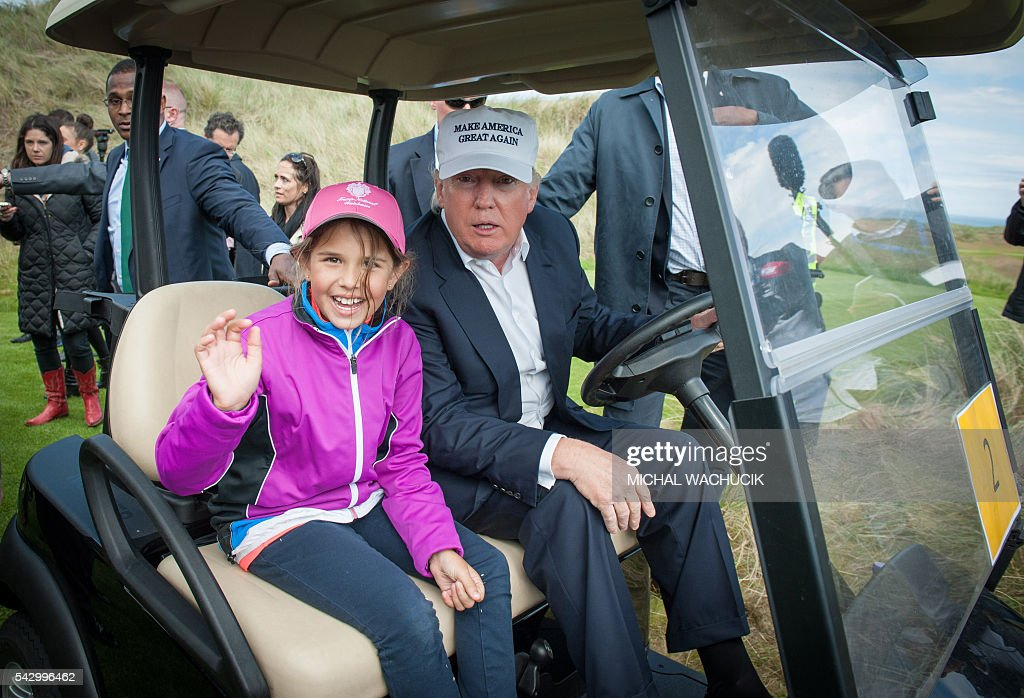 Presumptive Republican presidential nominee Donald Trump travels in a buggy with his granddaughter Kai during a tour of his International Golf Links course north of Aberdeen on the east coast of Scotland on June 25, 2016. Donald Trump hailed Britain's vote to leave the EU as 'fantastic' shortly after arriving in Scotland on Friday for his first international trip since becoming the presumptive Republican presidential nominee. / AFP / Michal Wachucik