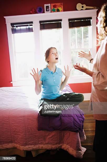 Preteen girl arguing with mother in bedroom