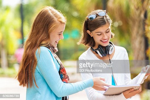 Preteen girl asking friend to borrow homework notes after school