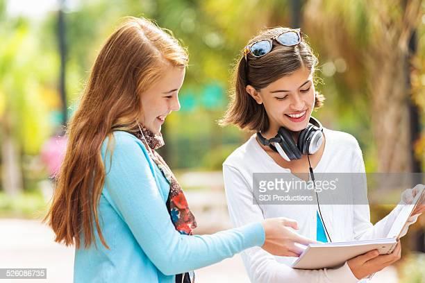 Preteen fille posant ami pour emprunter devoirs notes après l'école
