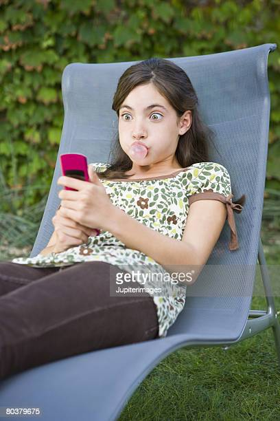 Preteen girl blowing gum bubble and texting
