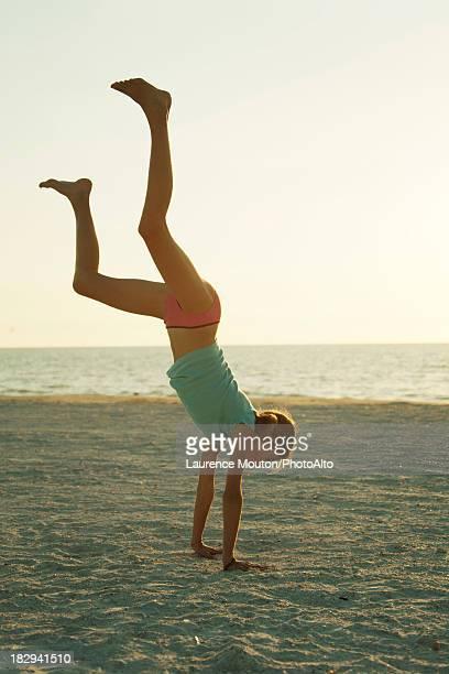 Preteen girl doing cartwheel at the beach