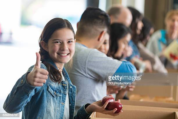 Preteen girl giving thumbs up while volunteering to sort donations